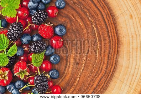 Fresh juicy berries with green leaves on wood texture