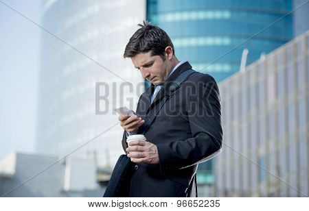Attractive Businessman Checking Text Message On Mobile Phone Outdoors