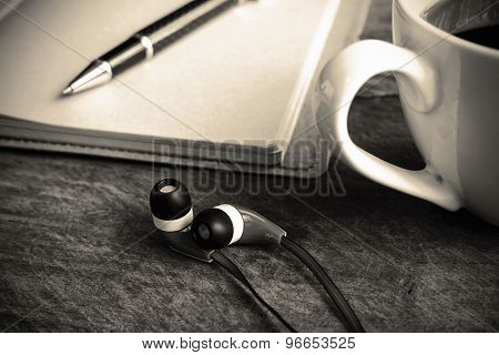 Close Up Of Earphone With Coffee And Notebook On Old Wooden Table, Sepiatone