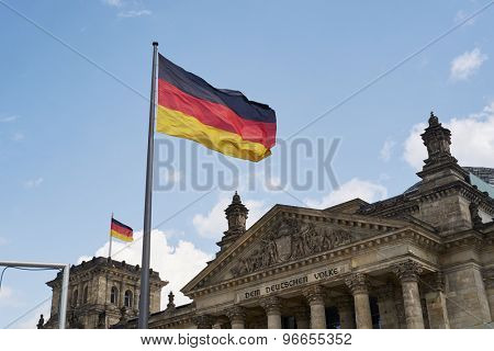 BERLIN, GERMANY - JULY 08: German flag blowing in the wind in front of the Reichstag building. July 08, 2015 in Berlin.