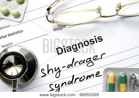 Diagnosis shy-drager syndrome and tablets on a wooden table.