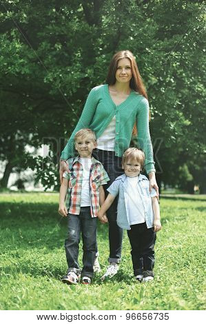 Happy Family! Mother With Two Children Sons Walks On Nature Together Hugging Standing On The Grass I