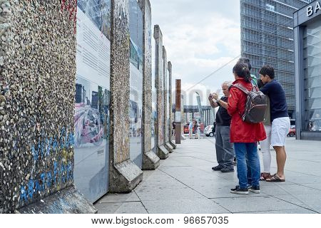 BERLIN, GERMANY - JULY 08: Tourists looking at remaining segments of the wall in central East Berlin. July 08, 2015 in Berlin.