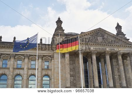 BERLIN, GERMANY - JULY 08: German and EU flags blowing in the wind in front of the Reichstag building. July 08, 2015 in Berlin.