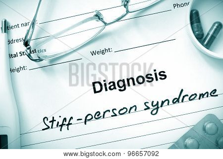 Diagnosis Stiff-person syndrome and tablets on a wooden table.