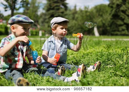 Portrait Of Two Boys Children Sitting On The Grass Blowing Soap Bubbles, Playing And Having Fun Toge