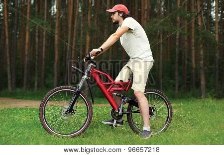Sport, Leisure And Healthy Lifestyle Concept - Young Handsome Bearded Man Sitting On A Bicycle In Th
