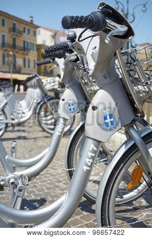 VERONA, ITALY - JULY 11: Low angle cropped shot the city's cycle hire bicycles parked in line. July 11, 2015 in Verona.