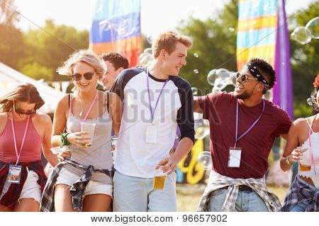 Friends walking together through a music festival site