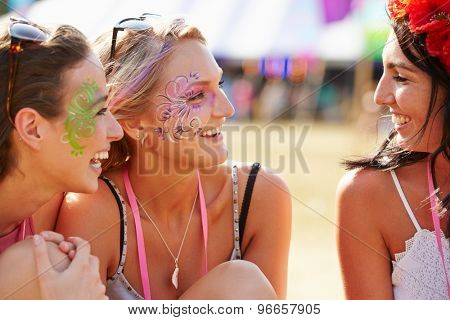 Girl friends wearing face paint at music festival, close up