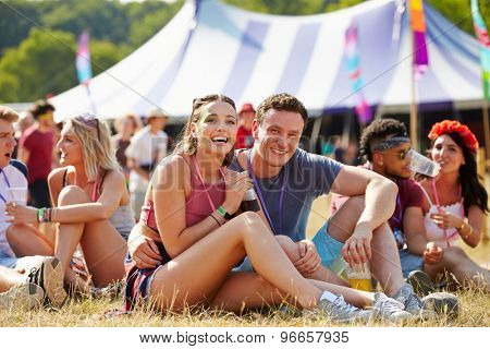 Couple sitting on grass in the audience at a music festival