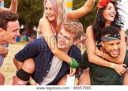 Friends giving piggy backs at a music festival