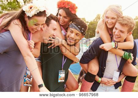 Friends giving piggy backs through music festival campsite