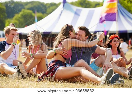 Couple sitting on the grass embracing at a music festival