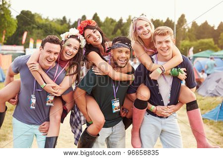 Friends giving piggy backs through music festival campsite