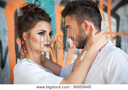 Brunette woman with aggressive makeup hugging man. Sexual young couple against graffity wall.
