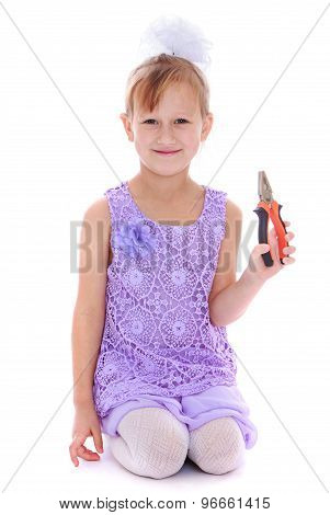 Little girl holding a pair of pliers