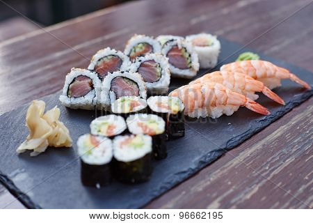 Three different kinds of sushi on a rock plate