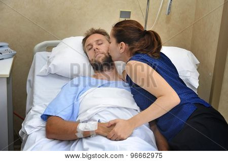 Couple At Hospital Room Man Lying In Bed And Woman Holding His Hand Caring