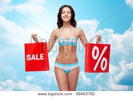 people, fashion, swimwear, summer sale and beach concept - happy young woman in bikini swimsuit with red shopping bags over blue sky and clouds background