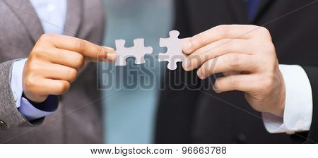 business and office concept - businessman and businesswoman trying to connect puzzle pieces in office