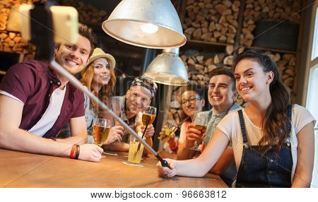 people, leisure, friendship, technology and communication concept - group of happy smiling friends with smartphone on selfie stick and drinks taking picture at bar or pub