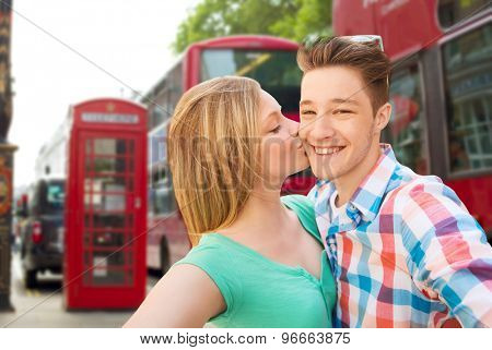 travel, vacation, technology and friendship concept - happy couple taking selfie over london city background