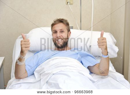 Young American Man Lying In Bed At Hospital Room Sick Or Ill But Giving Thumbs Up Smiling Happy And