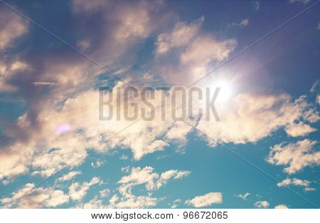 Cloudy blue sky with bright sunburst as the sun peeks out above a cloud in a nature and weather concept. Retro Effect.