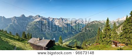 Rustic log cabins on an Alpine plateau near Hochvogel, Germany, overlooking a scenic panorama of forested slopes and rugged mountain peaks