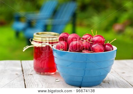 Fresh crabapples with jars of crabapple jelly.