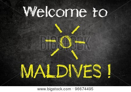Welcome to Maldives Message for Summer Vacation Concept Written on a Black Chalkboard with Glowing Sun Drawing in the Middle.