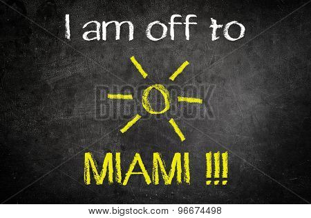 I am Off to Miami Message for Vacation Concept Written on a Black Vintage Chalkboard with Glowing Sun Drawing in the Middle of the Texts.