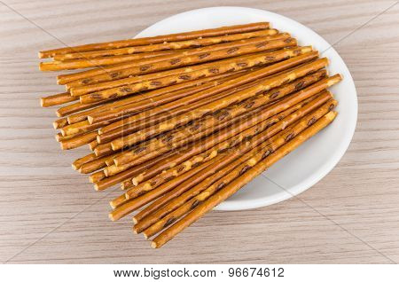 Salty Bread Sticks In White Glass Saucer On Table