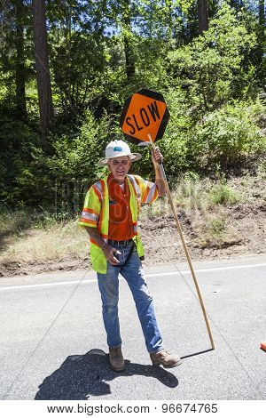 Street Worker Shows Slow Sign To Reduce Speed