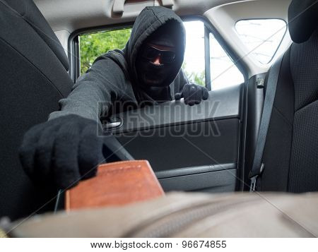 Crime concept. Burglar taking wallet from car.