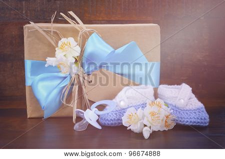 Baby Shower Gift With Booties On Dark Wood