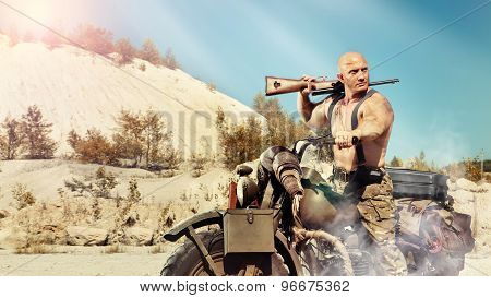 Muscular Bald Biker With The Rifle