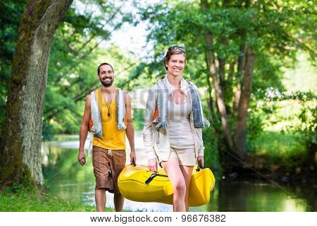 Man and woman carrying canoe to forest river