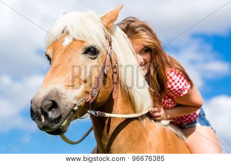 Woman riding on horse in summer meadow