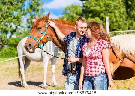 Couple petting horse on pony stable