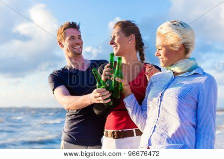 Friends enjoying bottled beer at sunset on German north sea beach