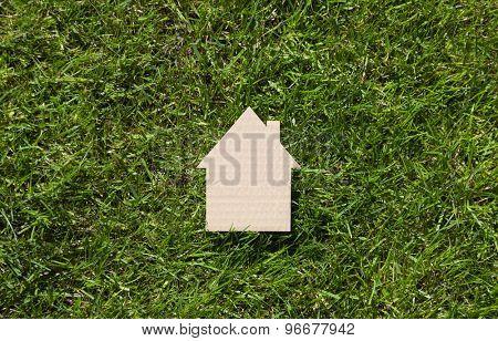 Cardboard house on green grass