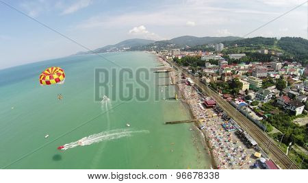 People fly by parachute near beach with many tourists at summer sunny day. Aerial view. Photo with noise from action camera.