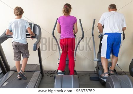 family of three on treadmills in a gym