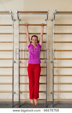 woman hanging on a horizontal bar in a gym