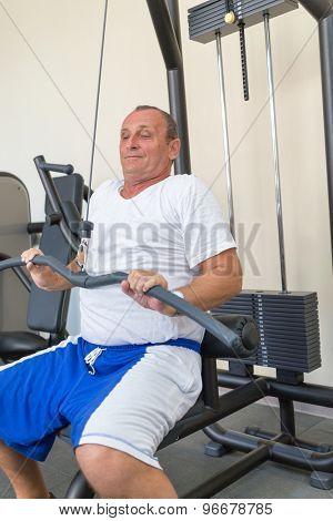 elderly man on weight machine in gym