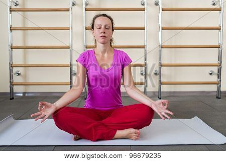woman meditating on the floor in the gym