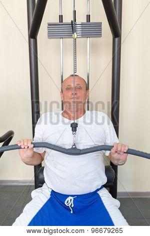 elderly man on weight machine in the gym