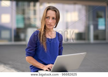 Woman Working On A Laptop On Her Lap